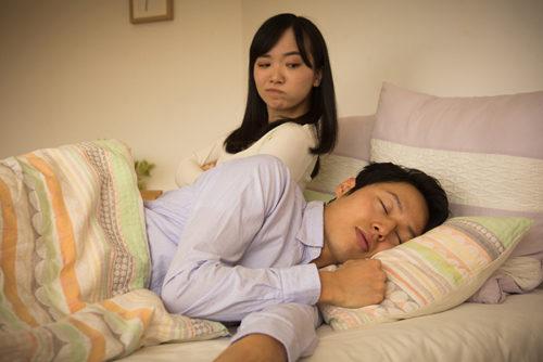 ベッドで寝ている男性を見る女性